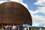 """A tour group going into the domed hall containing the """"Universe of Particles"""" exhibit on Square Galileo Galilei at CERN, (Conseil Européen pour la Recherche Nucléaire), the European Organization for Nuclear Research, Geneva, Switzerland"""