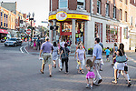 Several people crossing a busy street in Harvard Square