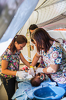 Nurse Sharon Pacaldo (left), of the Philippine Red Cross, treats at a severely dehydrated child together with other medical personnel in the emergency medical tent for evacuees in the city's largest stadium in Zamboanga, Mindanao, The Philippines on November 5, 2013. These Internally Displaced People (IDP) had taken refuge in this stadium after surviving the 3 week long attack by MNLF rebels. Photo by Suzanne Lee for SPRINT-IPPF