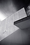 Black and white, upward- looking detail shot of 60's commercial building with dramatic dark sky and white clouds