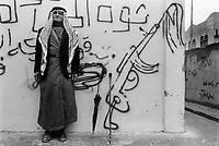 State of Palestine. West Bank. Balata Camp. Palestinian refugees. A muslim retired soldier wearing a keffiyeh on his head stands in the courtyard of an UNRWA building and poses close to a wall where an anonymous graffiti is asking for a free Palestine state by any possible means, even by using weapons such as Kalashnikov. Balata Camp is a Palestinian refugee camp established in the northern West Bank in 1950, adjacent to the city of Nablus. It is the largest refugee camp in the West Bank. Balata Camp is densely populated with 30,000 residents in an area of 0.25 square kilometers. In 1991, Balata Camp was living under Isreal's occupation and rules as part as the Occuppied Territories. In the 1980s and 1990s, Balata residents played a leading role in the uprisings known as the First Intifada and the Second Intifada. Balata Camp is since 1993 under palestinian authority, located in the A zone. The Palestinian National Authority (PA or PNA) was the interim self-government body established to govern Areas A and B of the West Bank as a consequence of the 1993 Oslo Accords. Following elections in 2006, its authority had extended only in areas A and B of the West Bank. Since January 2013, the Fatah-controlled Palestinian Authority uses the name State of Palestine on official documents. The Palestinian keffiyeh is a gender-neutral chequered black and white scarf that is usually worn around the neck or head. The Palestinian keffiyeh has become a symbol of Palestinian nationalism. The Palestinian keffiyeh is a gender-neutral chequered black and white scarf that is usually worn around the neck or head. The Palestinian keffiyeh has become a symbol of Palestinian nationalism. The AK-47 is a selective-fire, gas-operated 7.62×39mm assault rifle, first developed in the Soviet Union by Mikhail Kalashnikov. It is officially known in the Soviet documentation as Avtomat Kalashnikova . It is also known as Kalashnikov, AK, or in Russian slang, Kalash. © 1991 Didier Ruef