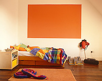 A painted abstract in bright orange is echoed in the bedside rug and accentuates the cosy atmosphere in this child's bedroom