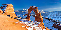 A panoramic view of Delicate Arch in Arches National Park in Utah at sunset with the La Sal Mountains in the background.