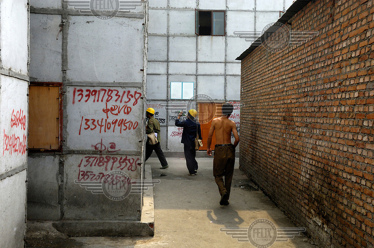 Temporary housing block built to house migrant construction labourers. On the walls are messages advertising services, ranging from fake IDs to electronic equiment for sale, with telephone numbers to call.