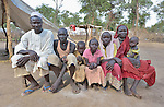 Haram Jukin (fifth from left), a ten-year old girl living in the Yusuf Batil refugee camp in South Sudan's Upper Nile State, poses with her family. More than 110,000 refugees were living in four camps in Maban County in October 2012, but officials expected more would arrive once the rainy season ended and people could cross rivers that block the routes from Sudan's Blue Nile area, where Sudanese military has been bombing civilian populations as part of its response to a local insurgency. Conditions in the camps are often grim, with outbreaks of diseases such as Hepatitis E. Her father Kames Jukin is on the left, and her mother Shaia Hamed in on the right.