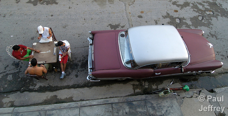 Youth playing dominos on the street in Cardenas, with an old car - a trademark of life in Cuba - beside them.
