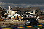 New Jersey, United States. 25th Feb, 2013 -- A car drive in front of a home destroyed almost 4 months ago by Sandy Storm at Jersey Shore in New Jersey. Photo by Eduardo Munoz Alvarez / VIEWpress.