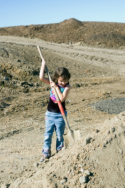 Emeryville CA Boy, four-years-old doing spontaneous digging with found shovel in construction site debris  MR