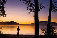 Camper watches morning fog at Dawn on Naknek lake, Kejulik mountains, Katmai National Park, Alaska.