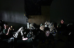 Lcpl. James Butson plays a video game on his Sony PSP as his comrades with Kilo Co. 3rd Battalion 1st Marines (3/1) read and relax in the company's base in the al-Anbar Province city of Hit, Iraq on Sun. Sept. 18, 2005.