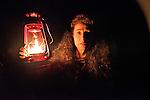 Woman and lamp. A woman walks with a kerosene lantern at night.