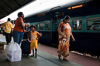 Razia Shabnam (in orange) boards a train with her son Saihaan, to referee an all-India invitational boxing competition in the neighbouring town of Burnpur, Calcutta, West Bengal, India. Razia Shabnam, 28, was one of the first women boxers in Kolkata. She was also the first woman in her community to go to college. She is now a coach and one of only three international female boxing referees in India. Photo by Suzanne Lee for Panos London