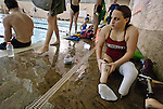 Lehi High School swimmer Amy Chapman attaches her prosthetic legs after finishing practice at the Lehi Legacy Center, Tuesday, Dec. 18, 2012. Chapman, 17, was born with fibular hemimelia and had both legs amputated when she was 13 months old.