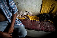 A Colombian urban shaman (brujo) sits on the sofa before starting the ritual of predicting the future in his house in Cali, Colombia, 17 April 2013. Although the original spiritual tradition, kept by the indigenous shamen in Americas for centuries, has been systematically repressed by the Catholic Church, nowadays, more and more people from the urban areas of Latin America discover their roots and consult their everyday problems with esoteric practitioners, healers and shamen. Traditional indigenous rituals (reading of tobacco - interpretation of signs shown by burn tobacco leaves) have merged with European concepts (divination using playing cards) and animistic religious beliefs (worshipping the spirits) brought to Americas by the African slaves, keeping the spirituality in modern Latin American society alive.