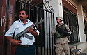 An Iraqi policeman and a U.S. soldier guard the scene of an attempted bank robbery in Baghdad, Iraq August 08, 2003.