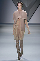 Iris Egbers walks runway in a nude melton cape jacket over nude silk chiffon long sleeve dress with cotton net insets and high neck collar, with nude techno stretch bermuda short, from the Vera Wang Fall 2012 Vis-a-gris collection, during Mercedes-Benz Fashion Week Fall 2012 in New York.