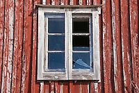 Broken window of traditional red painted building of the Lofoten islands, Norway