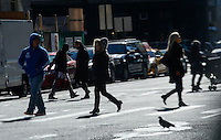 People walk by a street in Lower Manhattan while low temperatures affect the New York City area, 19 November 2014. Cold weather enveloped the entire country Tuesday, leading to record-low for November