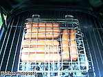 Cooking some turkey hot dogs in a food cage while grilling to perfection.