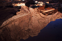 In the narrows confines of Horseshoe Canyon, in Utah's Canyonlands National Park, sunlight bounces off bright canyon walls and reflects in dark waters.