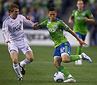 Seattle Sounders FC forward Miguel Montano passes the ball in front of Vancouver Whitecaps FC  defender Jonathan Leathers during play at Qwest Field in Seattle Saturday June 11, 2011. The game ended in a 2-2 draw.