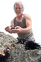 "Monemvasia, Peloponnesos, Greece, May 2013. Mountain man Christos carrefully opens a sea urchin to extract the ""caviar"", a local delicatesse. The hiking trail from Agios Fokas connects the area of Monemvasia with the Malea Peninsula and follows a rocky coastal trail passing several small beaches, to end at the Kastania Caves. The Peloponnese peninsula offers beautiful hikes along the bays and capes of the Mani and Monemvasia and the interior Taygetos. Venture inland, away from the crowds, and there are some surprises in store: snow-capped mountains, limestone gorges, shady rivers, crumbling castles, tower-villages, fir forests, frescoed chapels, and solated monasteries. Ancient mountain villages interrupt the olive groves that line the rugged coastline that is surrounded by deep blue and turquoise waters of the Mediterranean.  Photo by Frits Meyst/Adventure4ever.com"