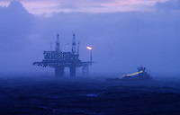 Oil production platform and safety boat during rain storm. North Sea.