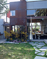 A small patch of lawn has been laid with crazy paving that leads up to the front of this modern house