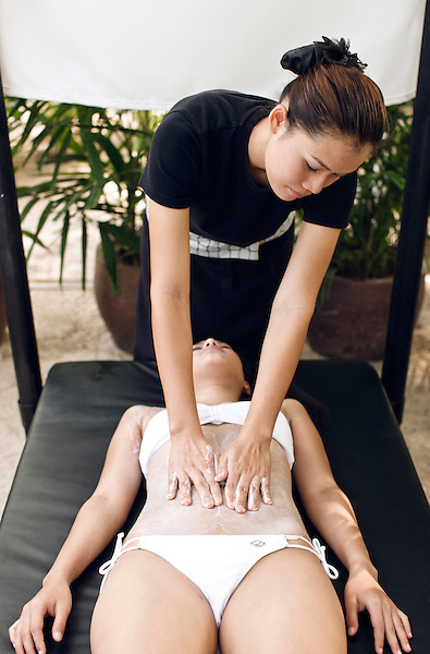 Woman Receiving Body Scrub at Indigo Pearl, Phuket, Thailand. A woman receives a Thai Rice Scrub at on outdoor beach cabana on Nai Yang Beach. The Thai Rice Scrub is a 30-minute full-body treatment offered by IN-DI-GO Spa that exfoliates the skin using a special cream made of ground Thai jasmine rice and apple and papaya extracts. Phuket, Thailand.