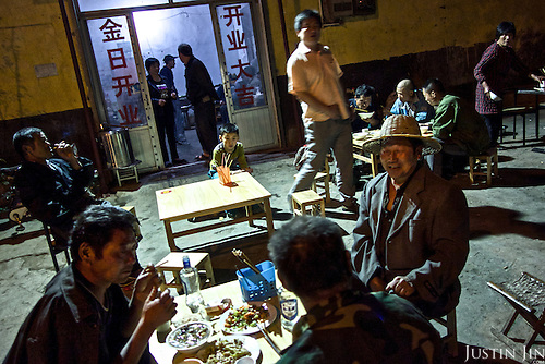 Rural migrants working on construction sites eat in a restaurant on the outskirts of a northeastern Chinese city.<br /> <br /> China is hoping by relocating farmers into cities they would start to buy food, making a break from the cycle of farmers consuming only what they produce.<br /> <br /> China is pushing ahead with a dramatic, history-making plan to move 100 million rural residents into towns and cities between 2014 and 2020 &mdash; but without a clear idea of how to pay for the gargantuan undertaking or whether the farmers involved want to move.<br />