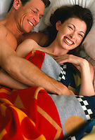 couple in bed wrapped in a blanket smiling and embracing