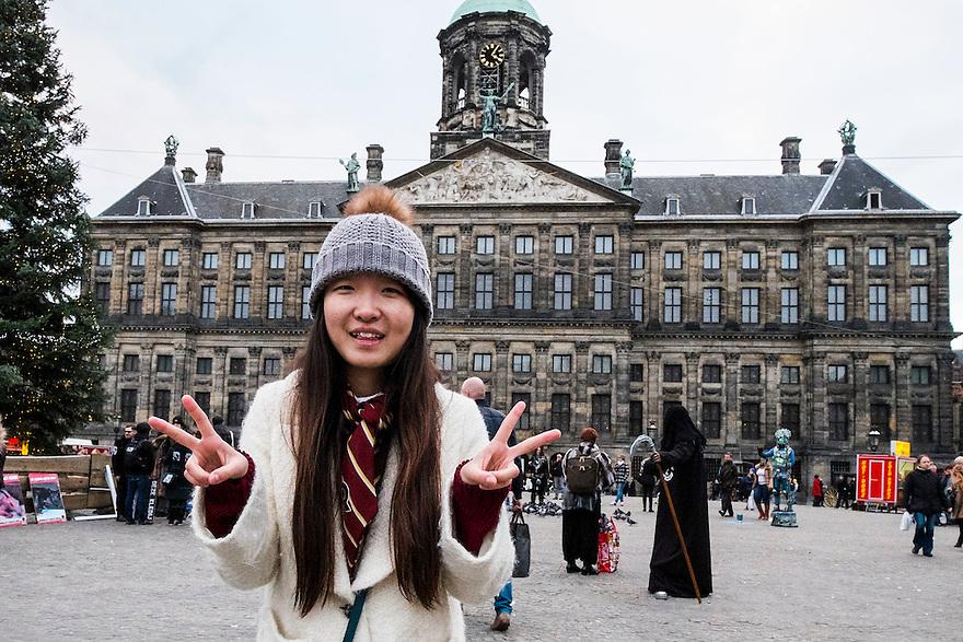 Nederland, Amsterdam, 13 dec 2014<br /> Chinese toeriste laat zich door haar vriendin fotograferen voor het paleis op de dam.<br /> Foto: (c) Michiel Wijnbergh