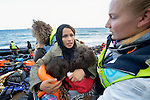 A mother hugs her children on a beach near Molyvos, on the Greek island of Lesbos, on October 31, 2015.  The family, part of a boatful of refugees that arrived from Turkey, were received by local and international volunteers (wearing yellow vests), then proceeded on their way toward western Europe. The boat was provided by Turkish traffickers to whom the refugees paid huge sums to arrive in Greece.