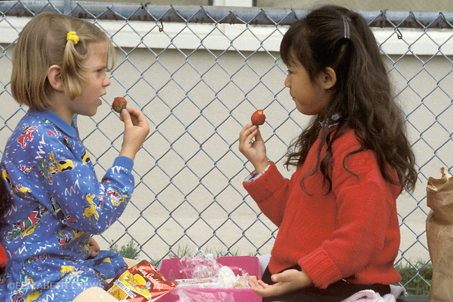 San Francisco CA Kindergarten friends having conversation while eating lunch together on school playground