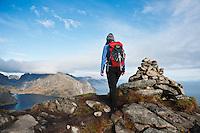 Female hiker walks near summit cairn on Reinebringen, Lofoten Islands, Norway