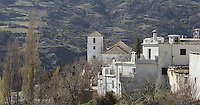 Bubion, with mudejar style Church of La Virgen del Rosari, 16th century, gorge of the Poqueira river, Alpujarra, Andalucia, Southern Spain. Moorish influence is seen in the distinctive cubic architecture of the Sierra Nevada's Alpujarra region, reminiscent of Berber architecture in Morocco's Atlas Mountains. Photograph by Manuel Cohen.