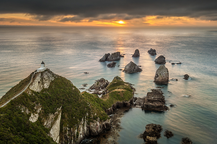 Nugget Point lighthouse at dawn looking out to sea. Catlins, Otago, South Island, New Zealand - stock photo, canvas, fine art print