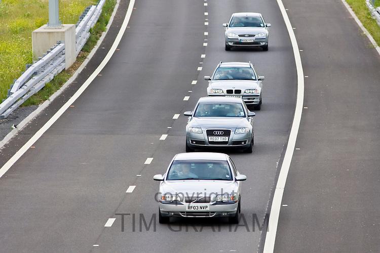 Cars motoring in the centre of the inside lane on M25 motorway slip-road, London, United Kingdom