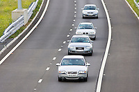 Cars motoring in the centre of the inside lane on M25 motorway slip-road, London, United Kingdom
