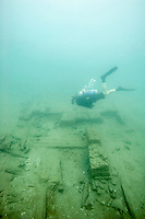 A man SCUBA dives on a 17th century wooden shipwreck in Panama. (Model Released)