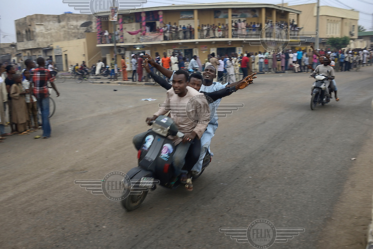 Jubilant youths ride their scooters through the streets of Kano as they celebrate the victory of Muhammadu Buhari, leader of the APC (All Progressives Congress Party), in the 2015 Nigerian Presidential elections.
