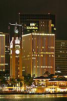 Night photo of Aloha tower and Aloha tower marketplace along Honolulu harbor. Downtown Honolulu in background. Oahu.