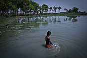 A swimmer walks across the pond to listen to the speech during the campaign rally of Bharatiya Janta Party's candidate, and minister of parliament, Yogi Aditya Nath in the outskirts of Gorakhpur, Uttar Pradesh, India.
