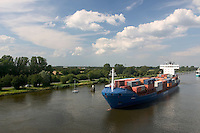 Cargo ship and sailboat along the Kiel Canal in Germany.