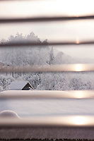 The snow-covered landscape beyond the chalet is glimpsed through the wooden slats of a Venetian blind
