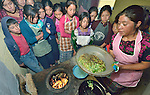 School children in Tuixcajchis, a small Mam-speaking Maya village in Comitancillo, Guatemala, learn about nutrition as they prepare and cook vegetables during class, with assistance from Reyna Tomas. The special program is sponsored by the Maya Mam Association for Investigation and Development (AMMID).