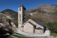 Low angle view of Sant Joan de Boi church, 1123, consecrated by Ramon Guillem, the bishop of Roda, Taull, Province of Lleida, Catalonia, Spain. It is a basilica with three naves with a central wooden gable roof apse and two small semi-circular apses. The first two storeys of the square bell tower are Romanesque and are decorated with Lombard arches; the last leg was added later.  Sant Joan de Boi church is part of the Catalan Romanesque churches of the Vall de Boí which were declared a World Heritage Site by UNESCO in November 2000. Picture by Manuel Cohen.