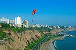 Paraglider flies over the Costa Verde overlooking the Pacific cliffs in the district of Miraflores in Lima, Peru.