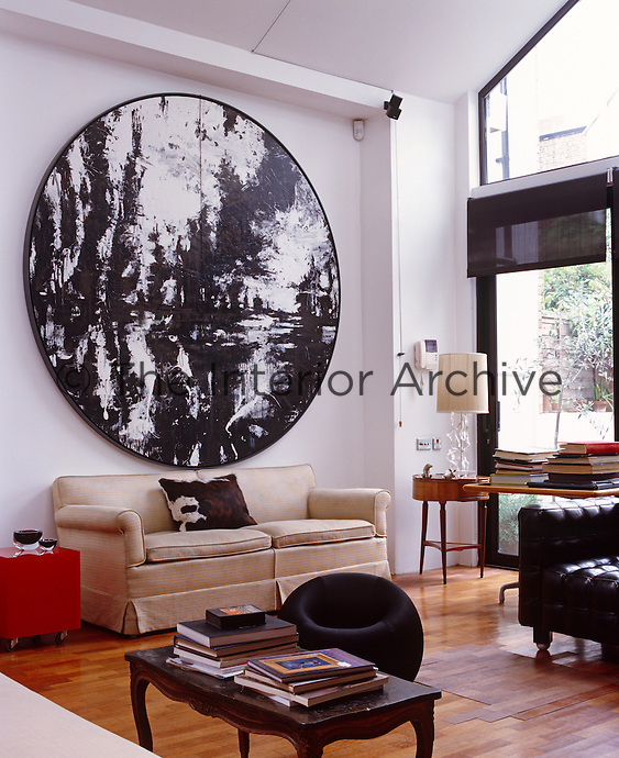 A circular painting by John Virtue dominates the light and airy living room