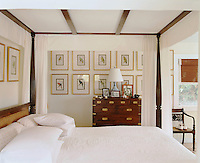 One wall in the bedroom is covered in a collection of gilt-framed prints depicting various species of parrot and creates a backdrop for a military chest